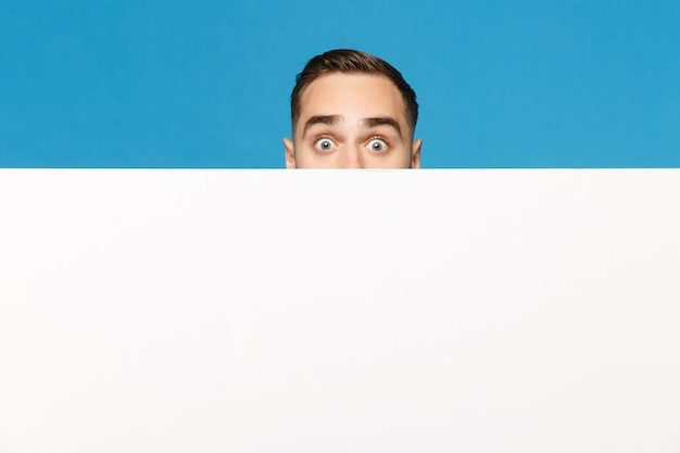 Giovane divertente che si nasconde, guarda fuori gli occhi grande cartellone bianco vuoto vuoto per contenuti promozionali isolati su sfondo blu muro ritratto in studio. concetto di stile di vita di emozioni di persone. mock up copia spazio.