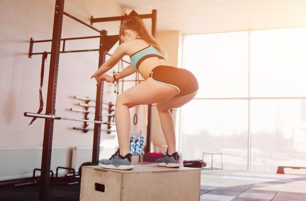 Formazione moderna funzionale. giovane donna bionda salta in uno squat su una scatola di legno alta in palestra. vista posteriore
