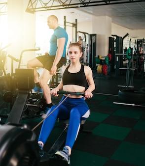 Concetto di allenamento funzionale. sport uomo e donna facendo esercizio in simulatore vogatore e air bike in palestra