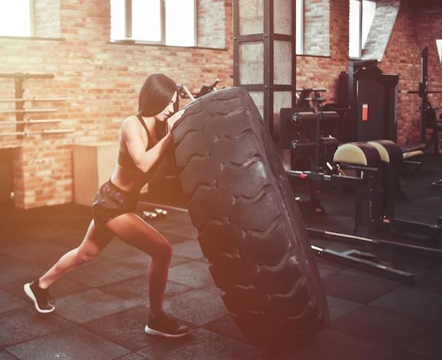 Concetto di allenamento funzionale. forte giovane donna castana che spinge una ruota pesante in palestra.