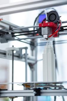 Funziona perfettamente. il primo piano di una moderna stampante 3d che crea un modello di grattacielo aggiungendo tutti i piccoli dettagli