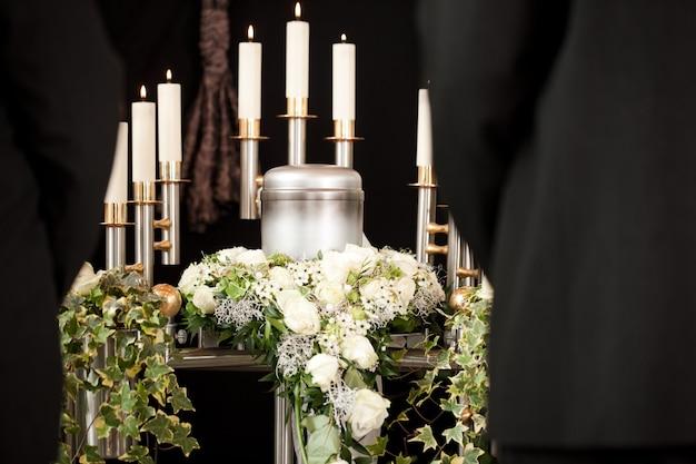 Urna funebre con candele e fiori