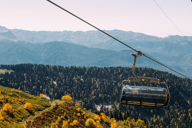 Funicolare alto nelle montagne sopra la foresta di autunno