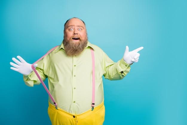 Uomo stupito funky che tira le bretelle punta il dito su sfondo blu copia spazio