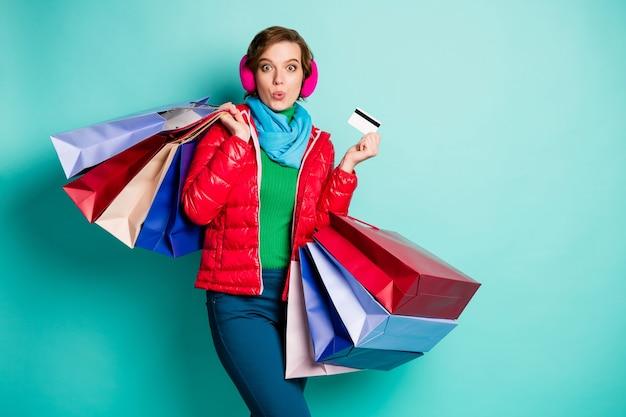 Funky impressionato ragazza studente centro commerciale cliente urla wow omg tenere borse pagare carta di credito indossare maglione verde pantaloni blu pantaloni cappotto esterno rosso isolato su muro color verde acqua