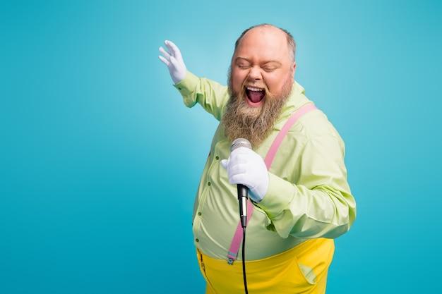 Uomo funky canta nel microfono divertendosi al karaoke su sfondo blu