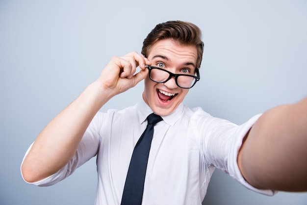 Umore funky di un giovane geek eccitato in occhiali e abbigliamento formale. sta facendo selfie scattati con la fotocamera, in piedi su uno spazio puro, scherzando