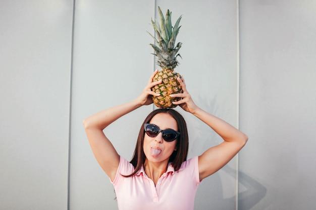 La ragazza adulta divertente si leva in piedi e tiene l'ananas sulla sua testa. indossa occhiali da sole. la donna mostra la sua lingua.