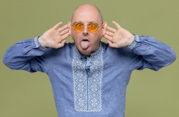 Un uomo adulto divertente con una maglietta blu che indossa occhiali da sole tira fuori la lingua e tiene le mani dietro le orecchie