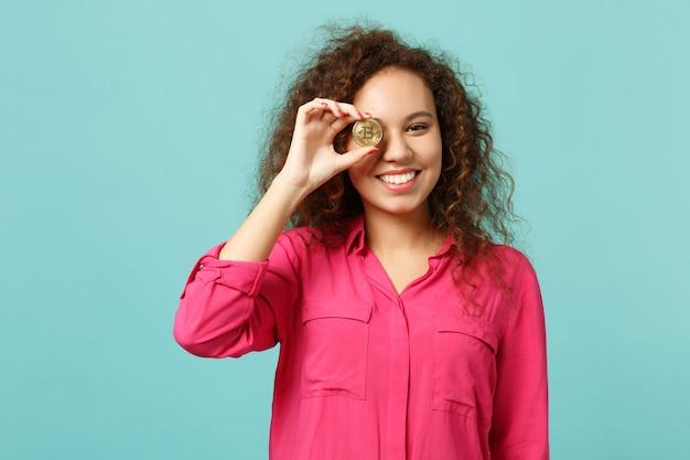 Divertente ragazza africana in abiti casual che tiene, coprendo l'occhio con bitcoin, valuta futura isolata su sfondo blu turchese in studio. concetto di stile di vita di emozioni sincere della gente. mock up copia spazio.
