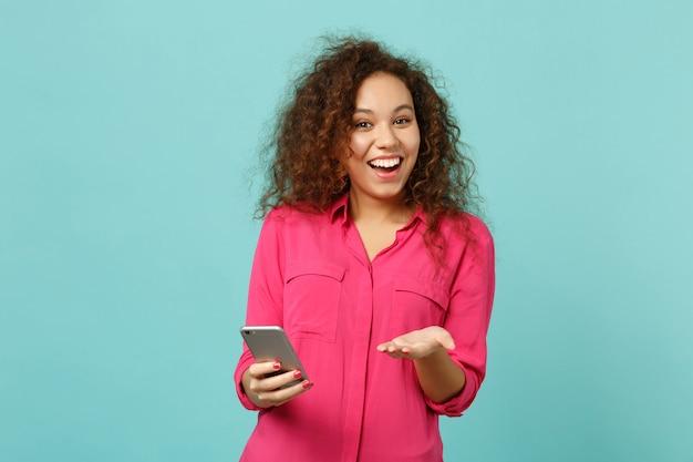 Ragazza africana divertente in abiti casual rosa utilizzando il telefono cellulare, digitando un messaggio sms isolato su sfondo blu muro turchese in studio. persone sincere emozioni, concetto di stile di vita. mock up copia spazio.