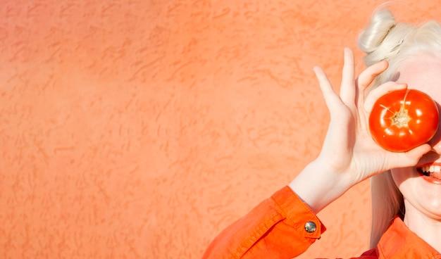 Giovane donna albino divertente in una camicetta rossa su sfondo rosso. tiene due pomodori rossi davanti ai suoi occhi e mostra la sua lingua copia spazio