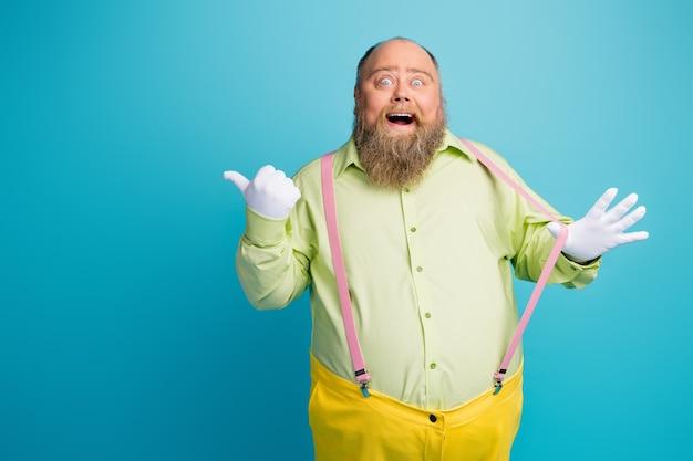 Divertente uomo stupito che tira bretelle pointinf dito copyspace su sfondo blu