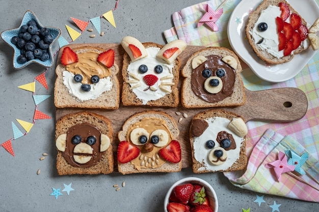 Animali divertenti facce toast con creme spalmabili, banana, fragola e mirtillo