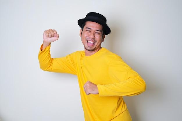 Uomo asiatico divertente che indossa vestiti gialli che balla felicemente