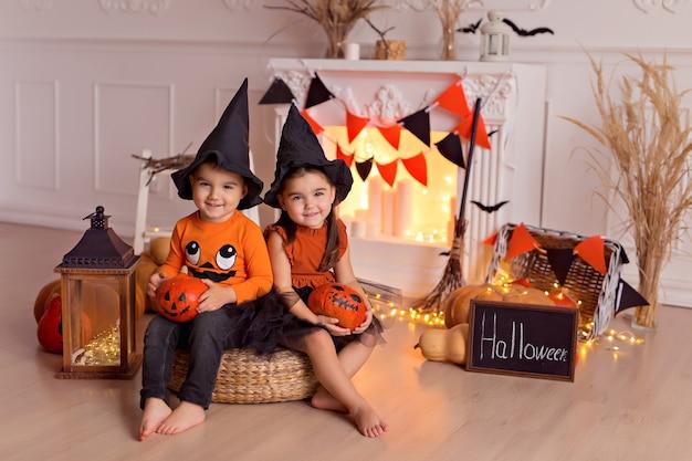 Neonato e ragazza divertenti in costumi della strega di halloween