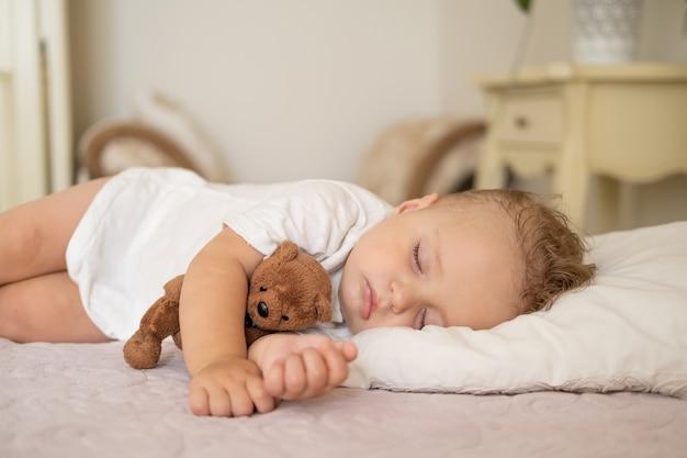 Neonato divertente che dorme sul letto a casa bambino che abbraccia orsacchiotto