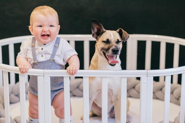 Neonato divertente che sta in greppia con il cucciolo sveglio