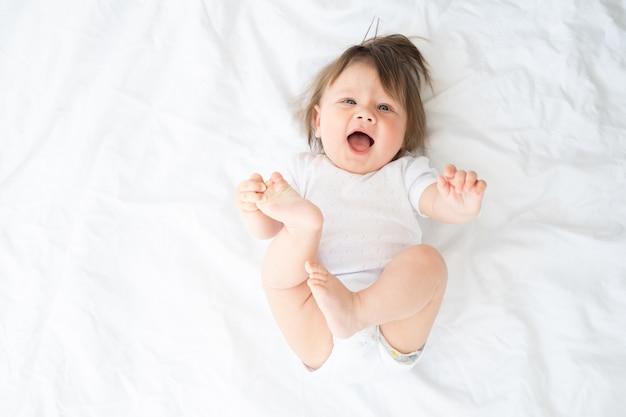 Neonato divertente in tuta bianca sorridente e sdraiato su una biancheria da letto bianca a casa. vista dall'alto.