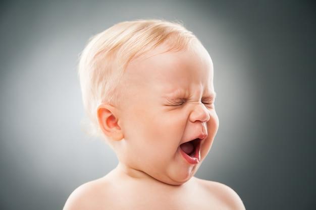 Funny baby strabismo occhi e apertura bocca.studio shot