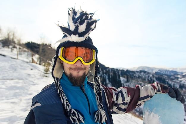 Il ritratto divertente dello snowboarder dell'uomo barbuto in cappello mohawk gode della stazione sciistica nelle montagne