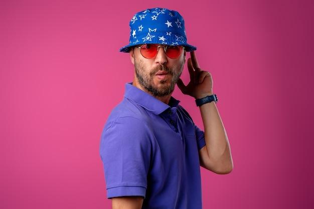 Uomo divertente di smiley barbuto che indossa cappello da spiaggia e occhiali da sole contro il rosa