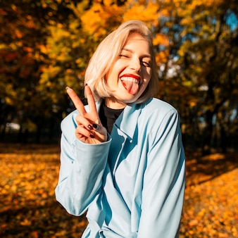 Divertente bella ragazza bionda felice in un cappotto alla moda mostra la lingua e il segno di pace nella natura autunnale con foglie gialle al tramonto