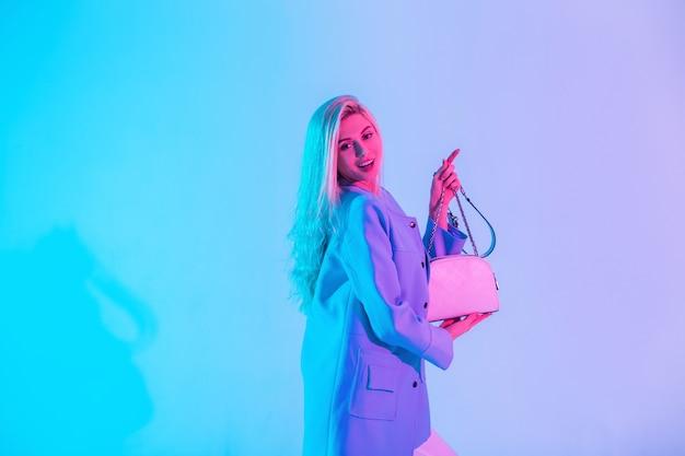 La bella donna bionda affascinante felice divertente con gode le emozioni in un blazer blu di moda tiene una borsa alla moda in uno studio su uno sfondo chiaro rosa al neon