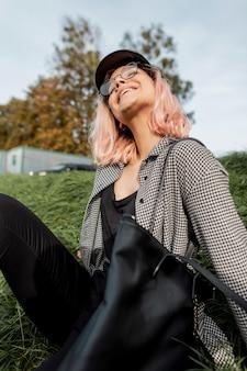 Divertente bella ragazza hipster felice con gli occhiali e un cappello vintage in una camicia a quadri alla moda con una borsa si siede e riposa sull'erba