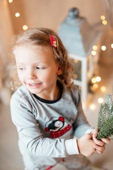 Divertente bella bambina in pigiama alla moda con rami di abete di natale sullo sfondo delle luci a casa. vacanze invernali