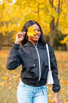 Divertente bella giovane ragazza afroamericana con un sorriso in abiti casual alla moda si copre gli occhi con una foglia gialla e cammina nel parco con fogliame autunnale dorato brillante