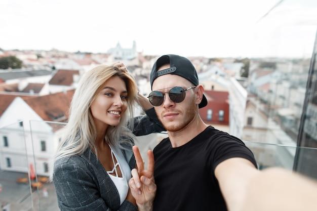 Belle giovani coppie divertenti che fanno selfie. bell'uomo con occhiali da sole mostra un segno di pace con una bella ragazza in viaggio in città
