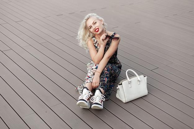 Divertente bella giovane donna modello con labbra rosse nella tavolozza vintage con motivo con scarpe di moda che si siede sul pavimento di legno. borsa bianca alla moda femminile