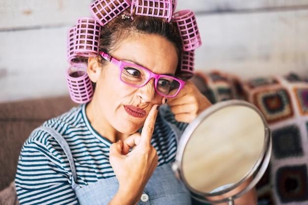 Divertenti e belli giovani di mezza età donna caucasica controllano la presenza di acne o rughe sul viso a casa - persone moderne in attività di benessere indoor - bigodini per il trucco di bellezza funzionano
