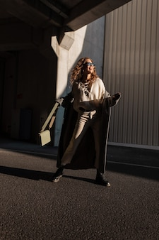 Divertente bella giovane donna sorridente con i capelli ricci in abiti alla moda guarda con un cappotto vintage, occhiali da sole, maglione, scarpe e una borsetta passeggiate in città in una giornata di sole. ragazza felice con un sorriso