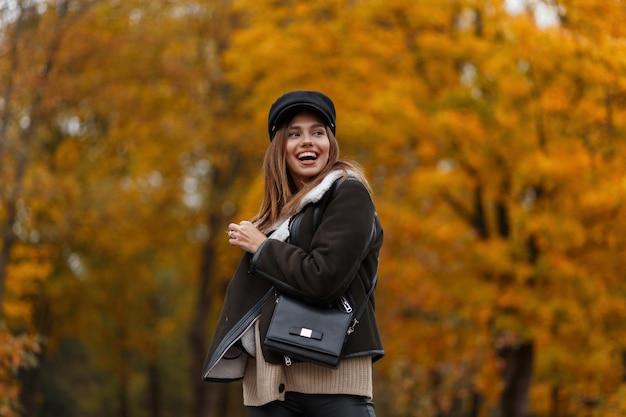 Bella giovane donna divertente in una giacca elegante marrone in un cappello elegante con una visiera con una borsa di moda in pelle in posa nel parco. ragazza felice con un sorriso carino in abiti autunnali alla moda all'aperto.