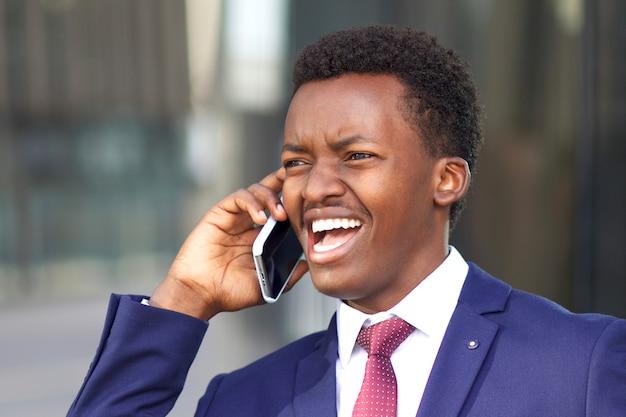 Uomo d'affari infastidito afroamericano africano nero divertente chiamando, parlando al cellulare, sostenendo, avendo una conversazione negativa, urlando