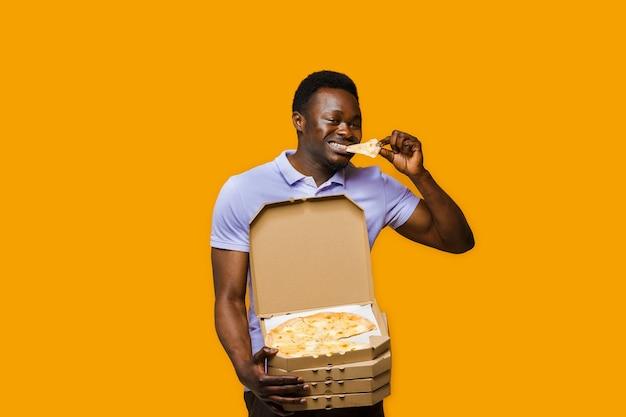 Il corriere nero divertente mangia un pezzo di pizza e tiene 4 scatole di pizza