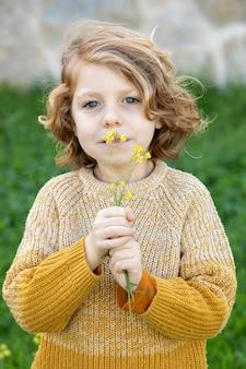 Ragazzo biondo divertente con capelli lunghi che odora un fiore