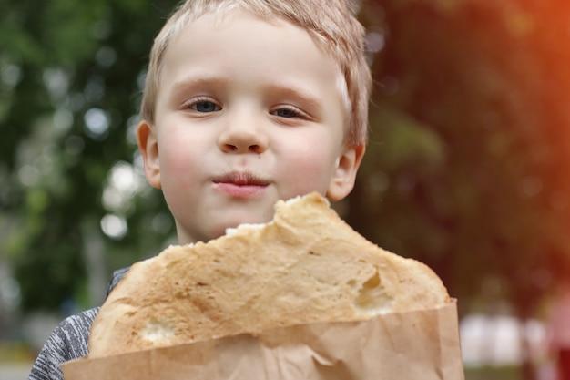 Un bambino divertente che mangia pane pita con appetito per strada e guarda la telecamera