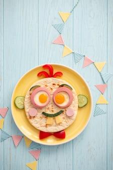 Divertente colazione per bambini con panino a forma di viso
