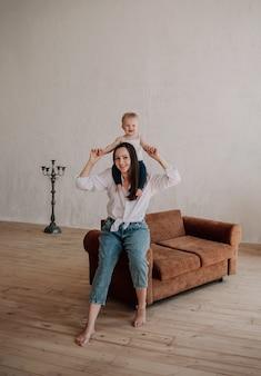 Divertente mamma bruna e bambina seduti su un divano marrone nella stanza