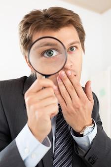 Uomo divertente di affari che tiene il ritratto della lente d'ingrandimento. investigazione investigativa privata, strato, criminalità, ricerca aziendale o concetto di sicurezza