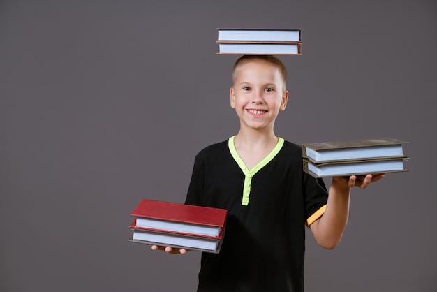 Il ragazzo caucasico divertente che tiene i libri nelle sue mani e sulla sua testa mostra la sua lingua su un fondo grigio...