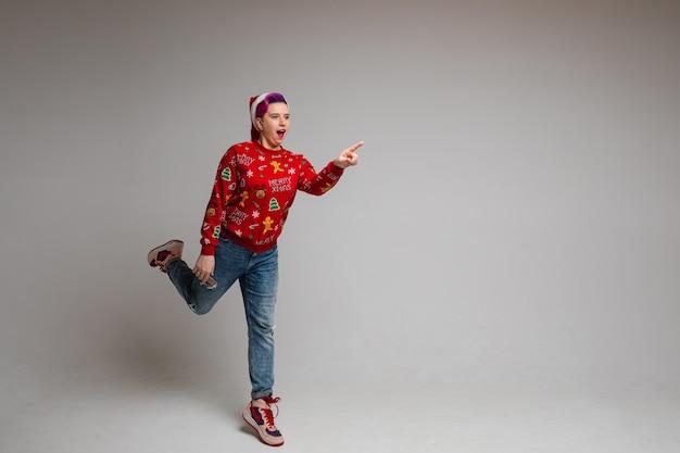 Femmina caucasica divertente in maglione rosso accogliente con stampa di natale, immagine isolata sulla parete bianca