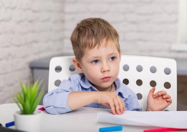 Bambino divertente che crea roba creativa bambino che taglia la carta delle forbici