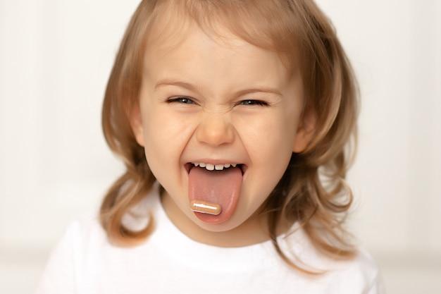 Ragazza divertente del bambino con la pillola sulla sua lingua che prende la medicina che prende le vitamine