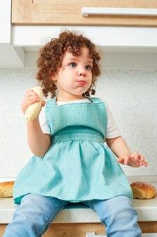 Una bambina divertente si siede su una scrivania con una banana in mano kushet cibo bambino riccio in cucina