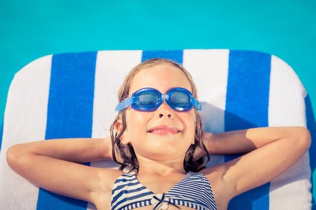 Bambino divertente sdraiato sul lettino in spiaggia contro l'acqua blu