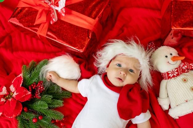 Un bambino divertente in un costume da babbo natale si trova su uno sfondo rosso tra i regali
